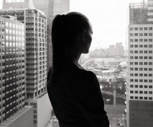 Woman look out of office window thinking.